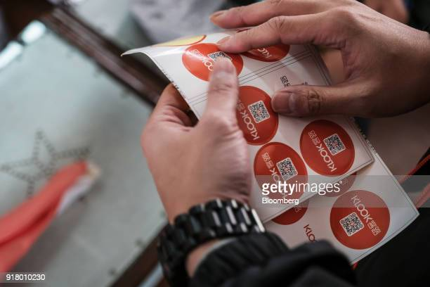 A tour guide handles stickers featuring quick response codes during a guided walking tour hosted by Klook Travel Technology Ltd in Hong Kong China on...