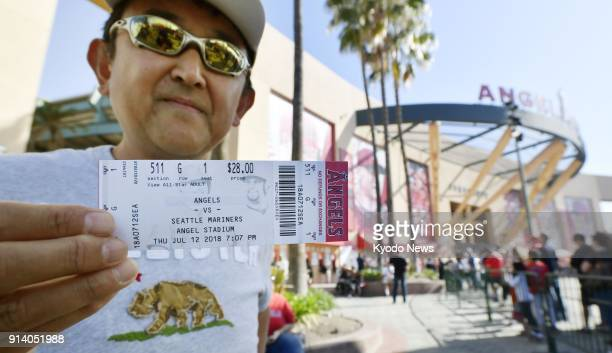 Tour guide Hikaru Baba shows off a ticket at Angel Stadium on Feb 3 for a game between the Los Angeles Angels and the Seattle Mariners for July 12...