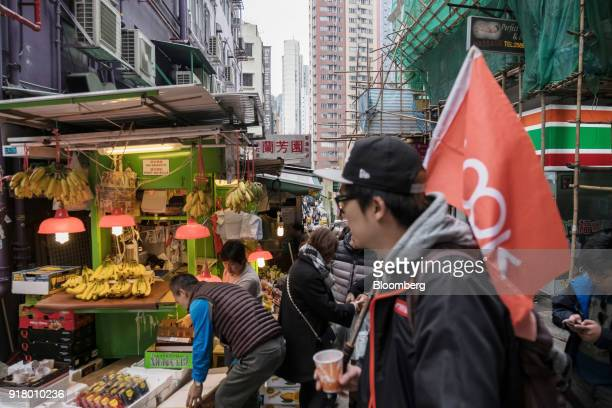 A tour guide holding a flag walks past a fruit stall as he leads a guided walking tour hosted by Klook Travel Technology Ltd in Hong Kong China on...