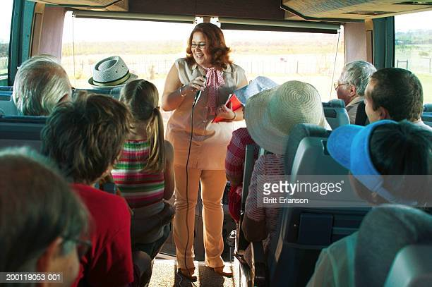 Tour guide holding microphone at front of coach full of tourists