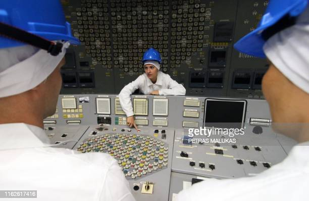 Tour guide Jurgita Norvaisiene points at a red button in the monitoring room during a guided tour inside the inoperative Ignalina nuclear power plant...
