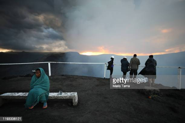 A tour guide keeps warm as tourists visit Mount Yasur volcano the main tourist attraction on the island on December 02 2019 in Tanna Vanuatu Tanna...