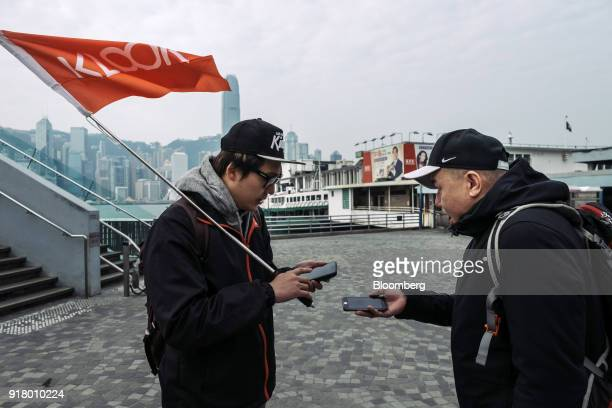 A tour guide left scans a quick response code on a tourist's smartphone during a guided walking tour hosted by Klook Travel Technology Ltd in Hong...