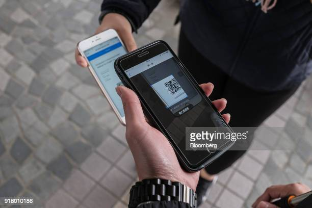 A tour guide scans a quick response code on a tourist's smartphone during a guided walking tour hosted by Klook Travel Technology Ltd in Hong Kong...