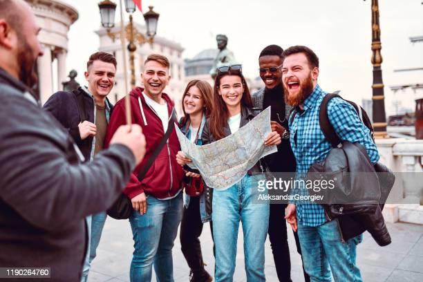 新しい観光客に都市を示すツアーガイド - ツアーガイド ストックフォトと画像