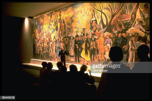 Tour guide standing in front of mural by artist Diego Rivera holding pointer giving lecture to onlookers at Del Prado Hotel