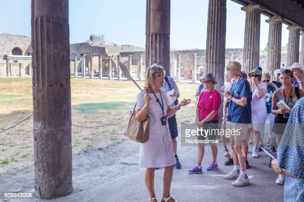 ポンペイの有名な遺跡の周りの観光客のグループを取るツアー ガイド