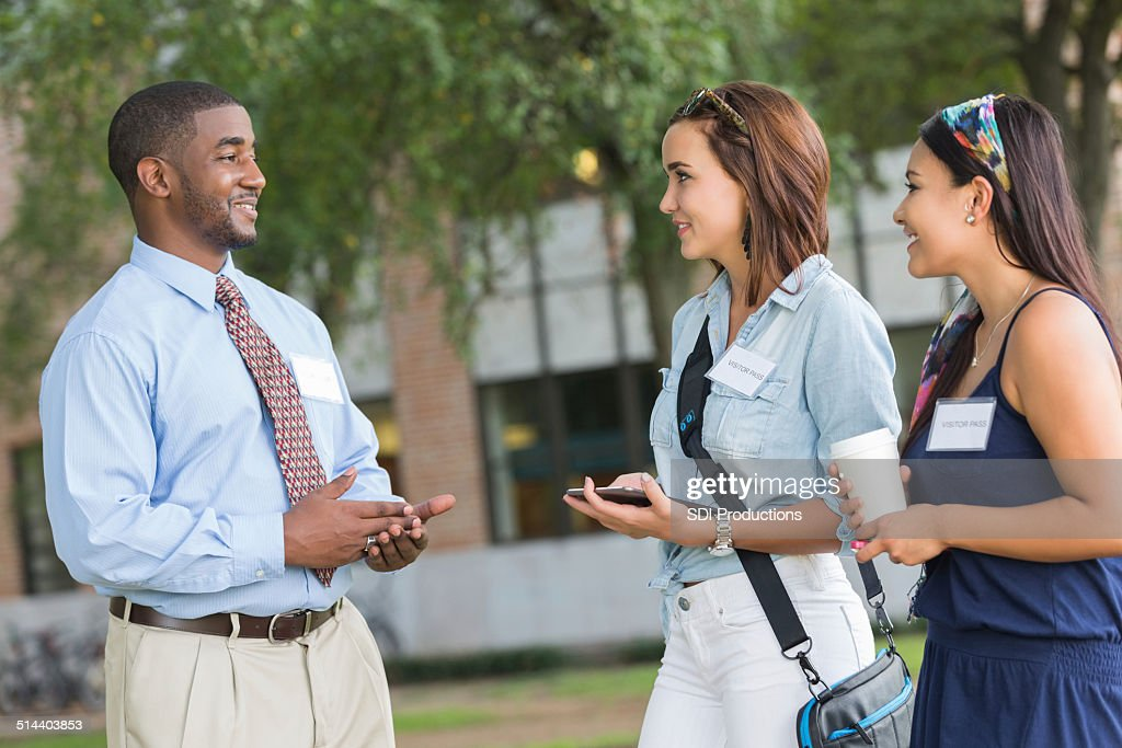 Tour guide talking to potential students while visiting campus : Stock Photo
