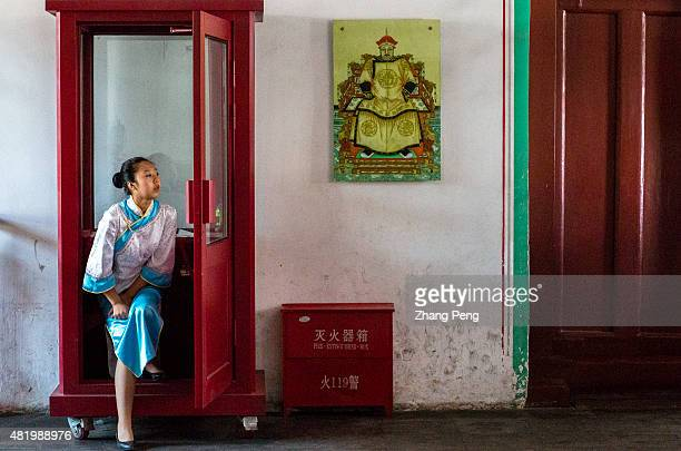 A tour guide wearing traditional Manchurian costume stands under the portrait of Huang Taiji in Qingning Palace Shenyang Imperial Palace built in...