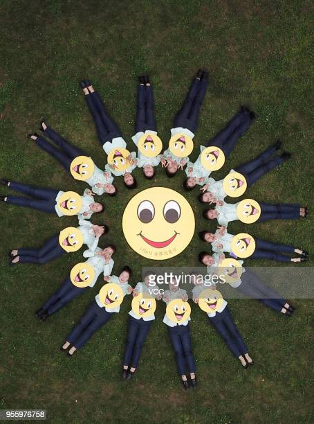 Tour guides from the Slender West Lake hold smiley face greeting cards to welcome the World Smile Day on May 8 2018 in Yangzhou China The World Smile...