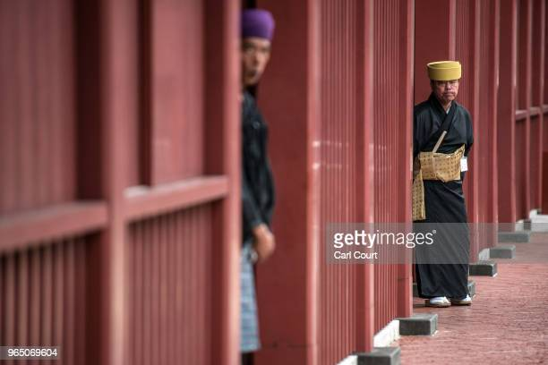 Tour guides in traditional Okinawan dress wait to help visitors to Shuri Castle on June 1 2018 in Naha Japan Like the rest of Japan the southern...