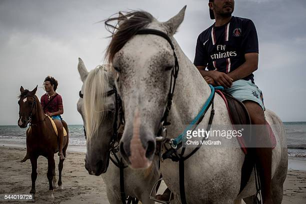 Tour guides wait to give tourists horse rides up the beach on June 30 2016 in Djerba Tunisia Before the 2011 revolution tourism in Tunisia accounted...