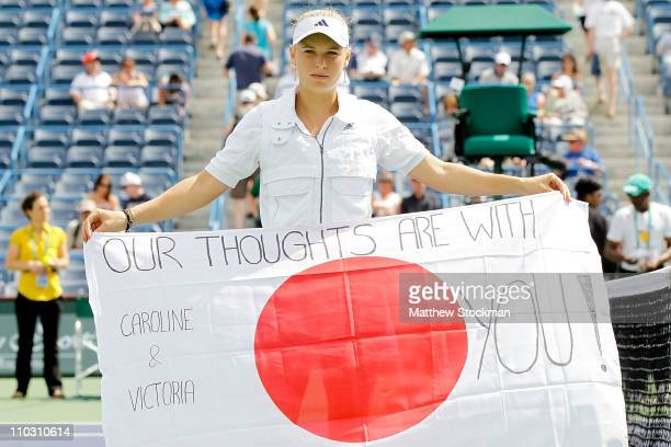 Tour player Caroline Wozniacki of Denmark holds a flag dedicated to the people of Japan after her match against Victoria Azarenka of Russia during...