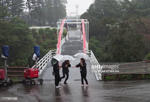 Tour staff of the PGA ZOZO Championship golf tournament walk in the rain at the Narashino Country Club in Inzai Chiba prefecture on October 25 2019