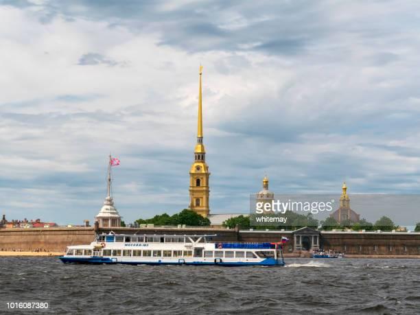 tourboat sobre o rio neva passando o peter e paul fortress em são petersburgo, rússia - peter forte - fotografias e filmes do acervo
