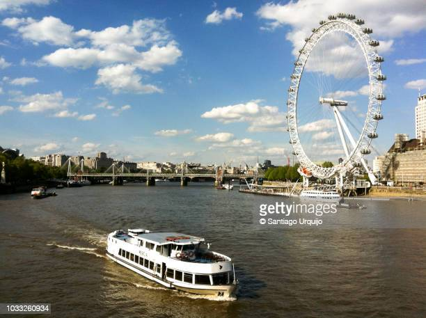 tourboat passing in front of the london eye millennium wheel - london eye stock photos and pictures