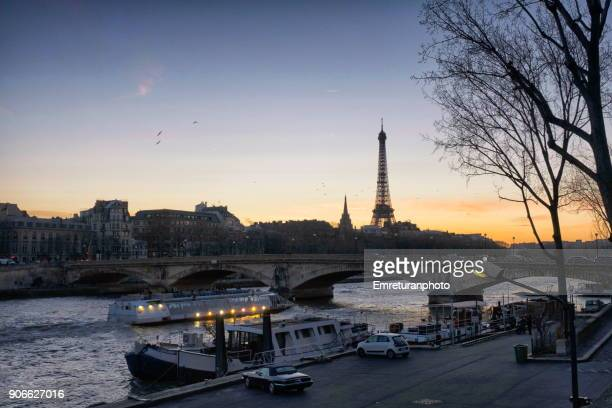 Tourboat passing under Invalides bridge with Eiffel tower at the background at sunset ,Paris.