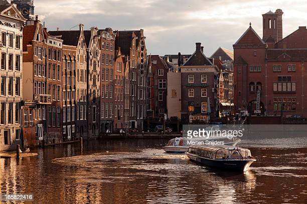 tourboat turns in the damrak canal - merten snijders stock pictures, royalty-free photos & images