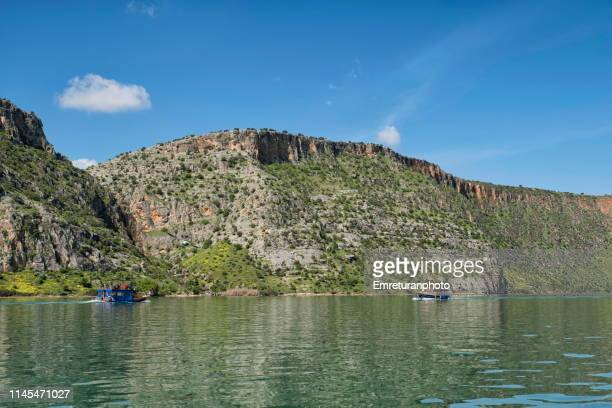 tourboats cruising in the water reservoir of birecik dam in şanlıurfa province.. - emreturanphoto stock pictures, royalty-free photos & images