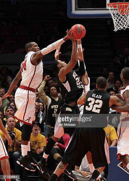 Toure' Murry of the Wichita State Shockers is stopped by Chris Hines of the Alabama Crimson Tide during the 2011 NIT Championship game on March 31...