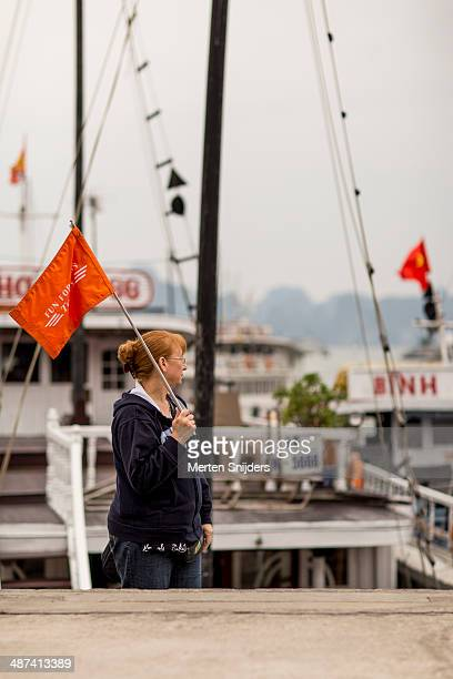 Tourguide with red flag at Ha Long harbour