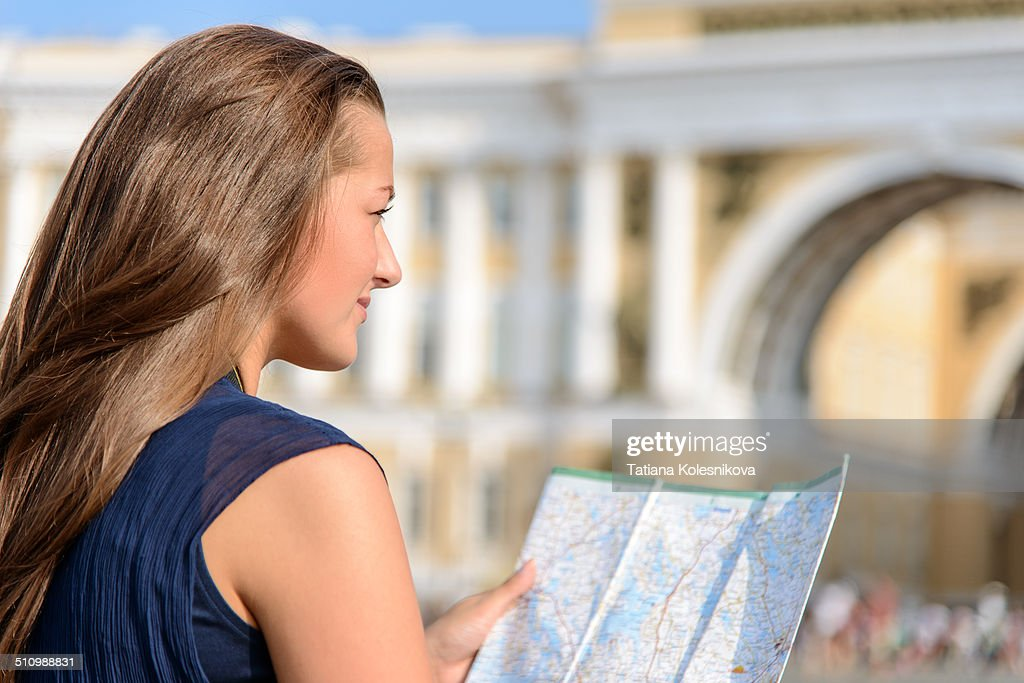 Tourism and travel concept. Young tourist, beautiful european girl sitting on pavement studying a map in the center of St.-Petersburg with Double Triumphal Arch on backgruond.