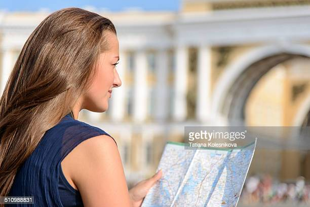 Tourism and travel concept. Young tourist, beautiful european girl sitting on pavement studying a map in the center of St.-Petersburg with Double...