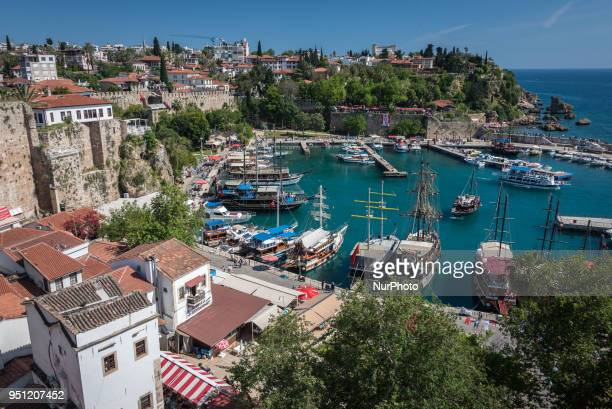 Tourism boats and ships dock between castle walls and traditional Ottoman houses in the Roman Harbor of Kaleici the historic old city of Antalya a...