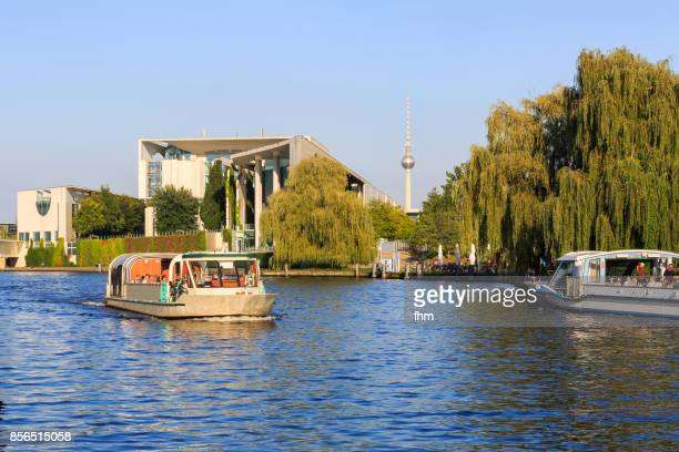 Tourism in Berlin - sightseeing boat on Spree river with chancellor's office and television-tower (Berlin, Tiergarten district, Germany)