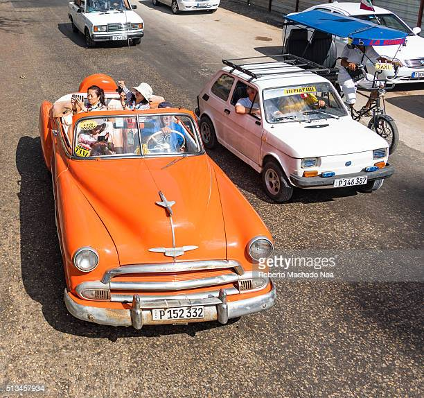 Tourism Old orange American convertible taxi cab with tourist taking pictures Riding down a sunny day