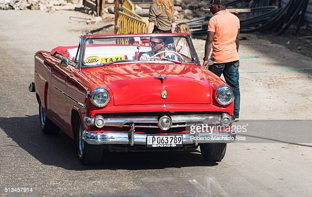 Tourism Old red American convertible taxi cab riding down the street on a sunny day