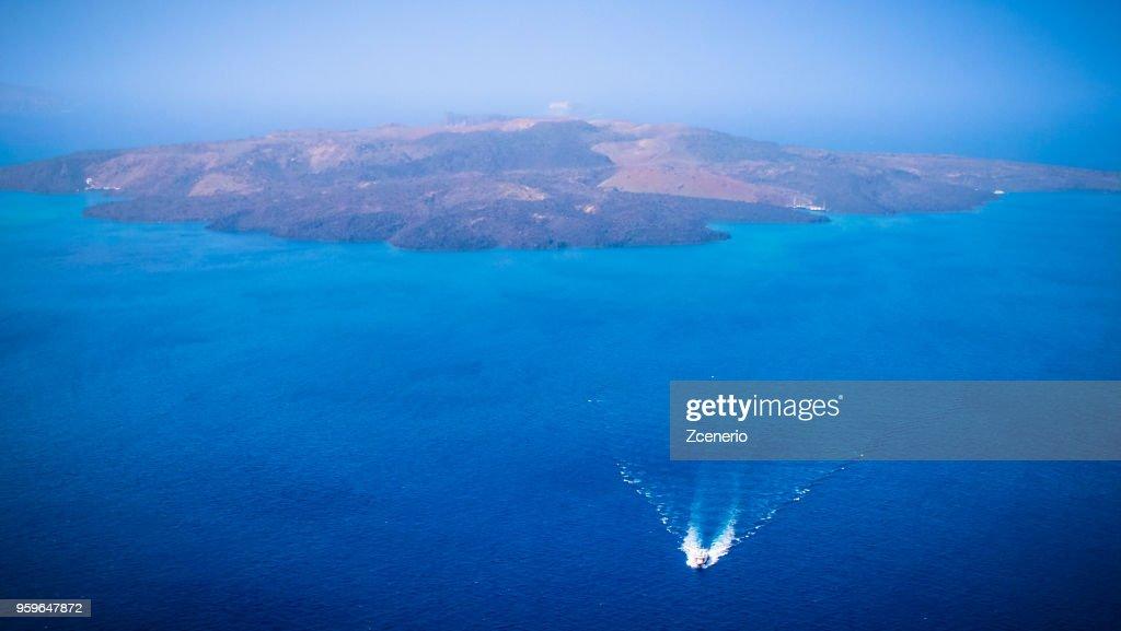 A tourism ship travelling between Santorini volcanic island and Thira (Fira) old port on Santorini island, Aegean sea, Mediterranean, Greece : Stock-Foto