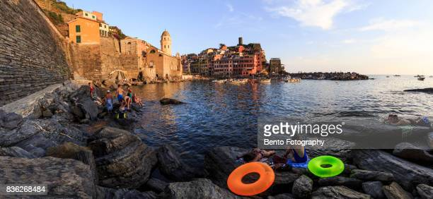 Tourism swimming and lying on the rock in Vernazza, Cinque terre, Italy