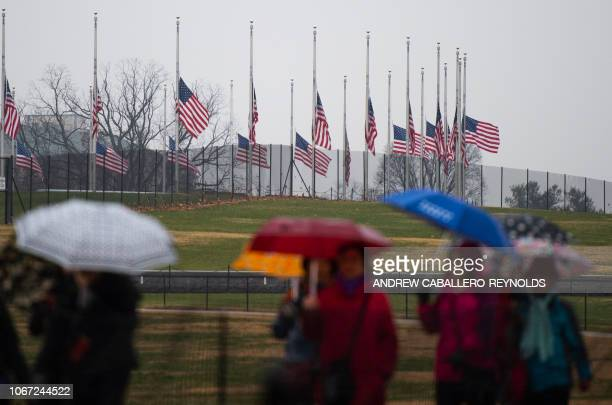 Tourisrs walk past that US flags fly at halfstaff at the Washington Monument in tribute to former US President George H W Bush on December 1 in...