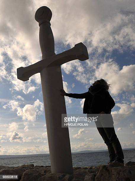 A tourist admires a huge stonemade replica of legendary King Arthur�s sword in the stone in southern Croatian coastal town of Podstrana some 400...