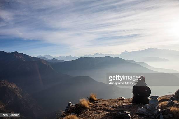 a tourist admires the himalayan sunrise in chopta, uttarakhand, india - uttarakhand stock pictures, royalty-free photos & images