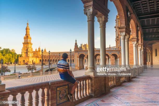 Tourist admiring Plaza de Espana from portico, Seville