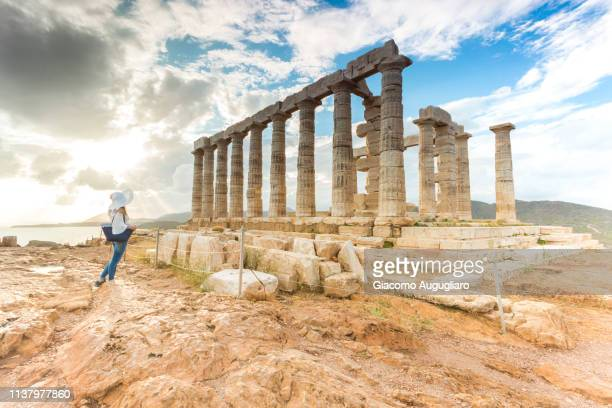 tourist admiring the ancient temple of poseidon at cape sounion, attic region, greece, europe - ancient civilization photos et images de collection