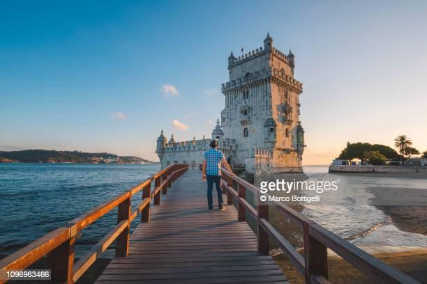 tourist admiring the belem tower at sunset, lisbon - città di lisbona foto e immagini stock