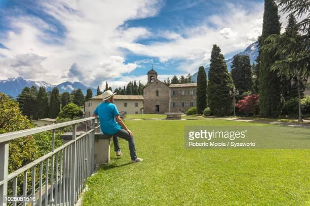 tourist admiring the old abbey, lecco, italy - nonnenkloster stock-fotos und bilder
