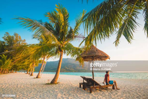 tourist admiring the sunrise from a deckchair on tropical beach, thailand - beach holiday stock pictures, royalty-free photos & images
