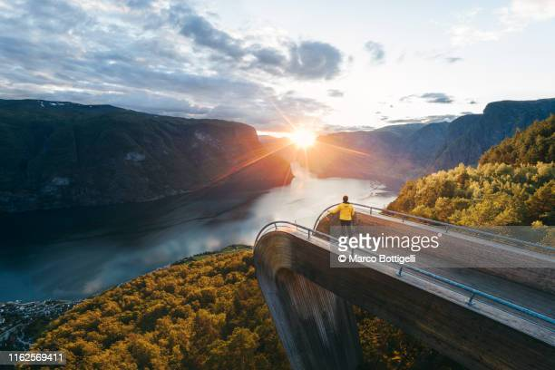 tourist admiring the sunset over norwegian fjord, norway - terrasse panoramique photos et images de collection