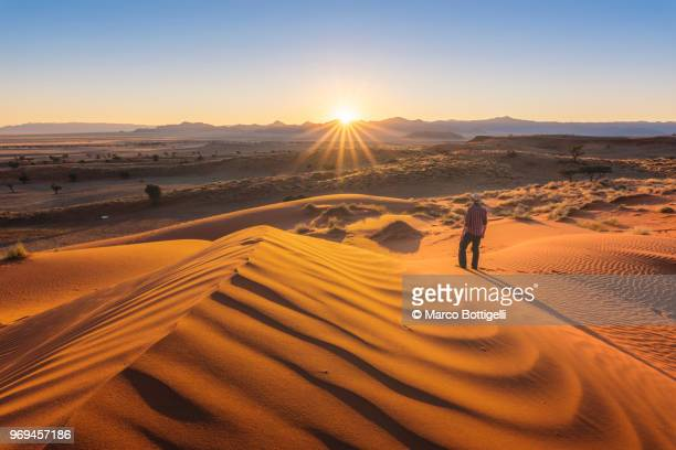 Tourist admiring the sunset over the Namib desert, Namibia