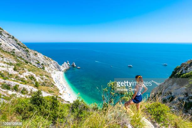 tourist admiring the two sisters beach (spiaggia le due sorelle). conero, italy - italy stock pictures, royalty-free photos & images