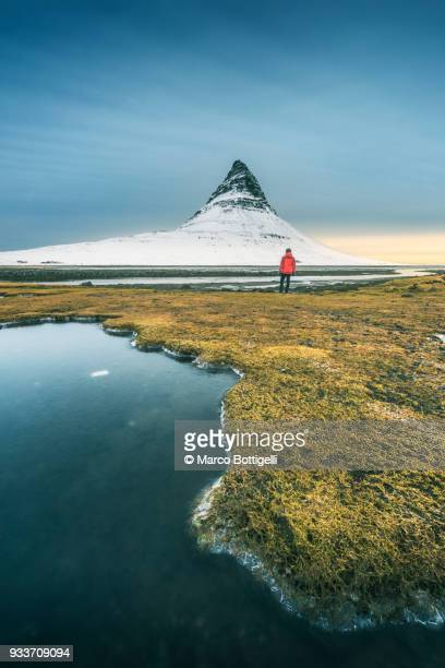 tourist admiring the view at kirkjufell mountain, iceland - middlebare afstand stockfoto's en -beelden
