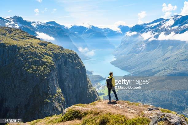 tourist admiring the view from the top of a mountain in loen, norway - norwegen stock-fotos und bilder