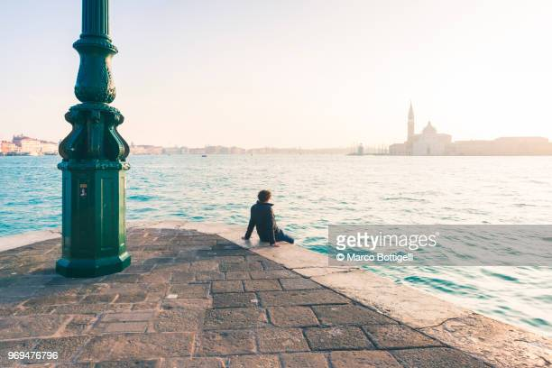 tourist admiring the view in venice, italy - punta della dogana stock photos and pictures