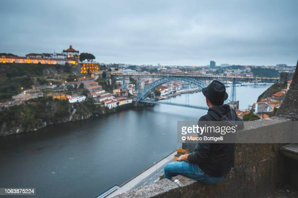 tourist admiring the view of dom luis i bridge and douro river at night - porto fotografías e imágenes de stock