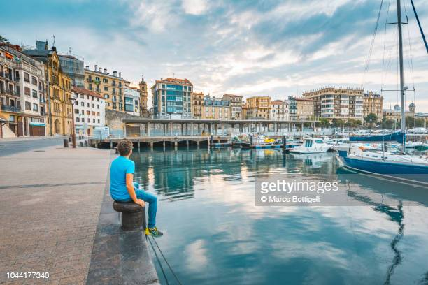 tourist admiring the view of the old town in san sebastian - san sebastian spain stock pictures, royalty-free photos & images