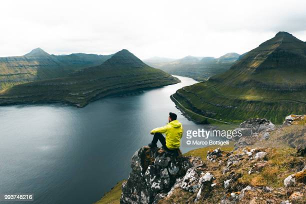 tourist admiring the wilderness in the faroe islands - islas faroe fotografías e imágenes de stock